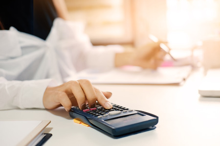Closeup woman calculate finance data with calculator on office table with morning light. Stock Photo