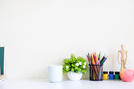 Mockup table with plant decorate, cup of coffee, water colour, jar of colour pencil and wooden model artist workspace.