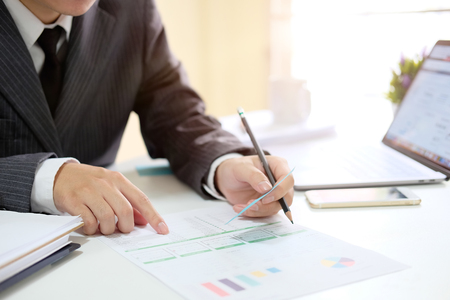 Business man analysis data in paper document with laptop computer in office. Stock Photo