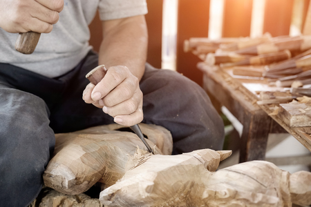 Closeup Old man Hands of craftsman wooden carve with a gouge in the hands on the workbench in carpentry