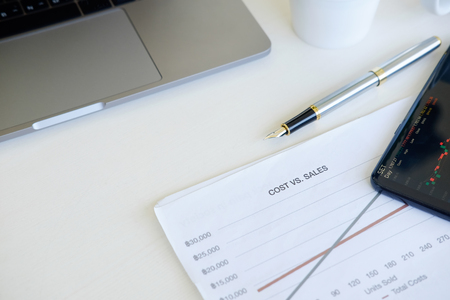 Cost financial concept, business equipment paper chart, pen with laptop computer and smartphone on office table. Stock Photo