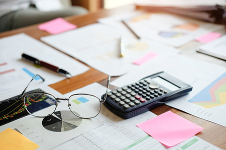 Finance concept, business equipment glasses, data financial paper and calculator on office table. Stock Photo