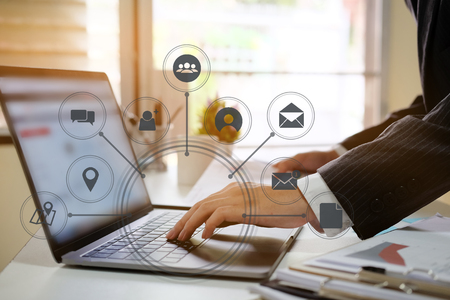 businessman hand working with laptop computer in modern office with virtual icon diagram at modern office in morning light Stock Photo