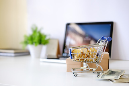 Shopping online concept, Money on Cart with box on office table.