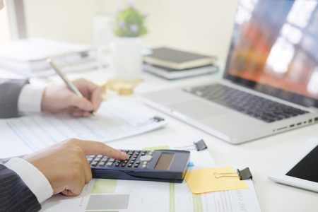 Cropped shot businessman calculate financial invest on calculator. Stock Photo