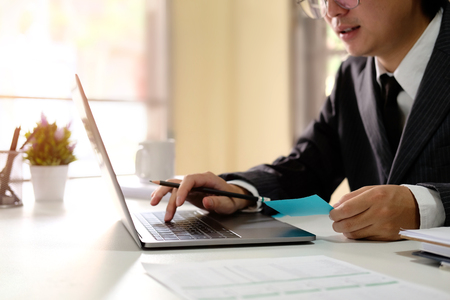Businessman working with computer laptop with lighting morning and side view photo. Stock Photo