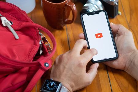 CHIANGMAI, THAILAND, 9. JULI 2018: Ein Mann, der einen Screenshot von Youtube auf dem neuen iPhone x zeigt. YouTube-App auf dem Bildschirm liegt auf alten Holzschreibtisch. YouTube ist die beliebte Online-Website zum Teilen von Videos.