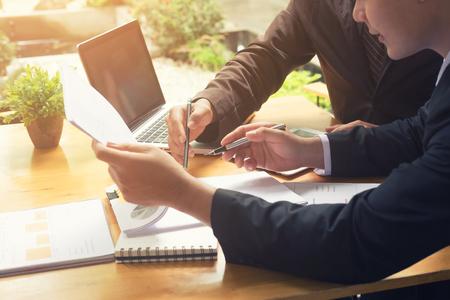 Dos hombres de negocios consultan informe financiero con una reunión de consultoría.