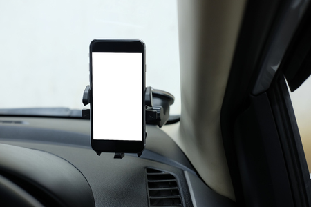 Mockup Smartphone in a car use for Navigate or GPS. Smartphone in holder. Mobile phone with isolated white screen.