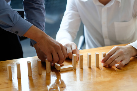 Businessman hand stopping the domino effect. executive and risk control concept. Stock Photo