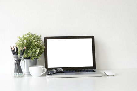 Workspace laptop computer, coffee cup and plant decorate on white office desk. Stock Photo