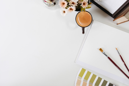 Top view office desk with designer table a Pantone, coffee and notebook paper sketch on white table artist workspace above view. Stock Photo