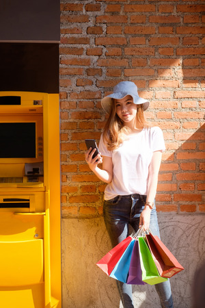 Shopping girl using smartphone near an automated teller machine with shopping bag on hand.