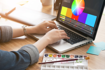 Cropped shot of a graphic designer using computer in her work on the foreground and working with color samples for selection. A concept of modern digital workplace.