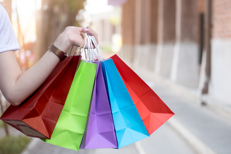Cropped shot of hand holding a shopping bag and blank space on blur shopping mall. Stock Photo