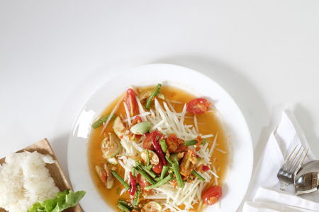 Som tam thai, green papaya salad on white table with space. Stock Photo
