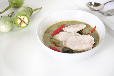 Green curry soup with top view on white table and copy space.