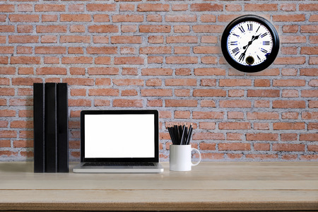 Mockup computer laptop with jar of pencil , document file folder and clock on brick wall on background.