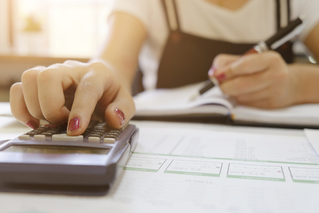 Female calculate finance data with cropped shot on calculator. Stock Photo