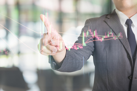 Businessman pointing a stock market graph on visual monitor. Stock Photo