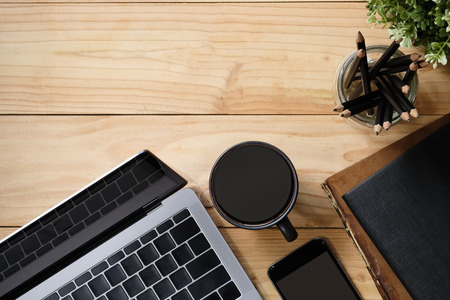 Office desk a laptop, coffee, book, pencil and smartphone on copy space workspace table top view with wood texture.