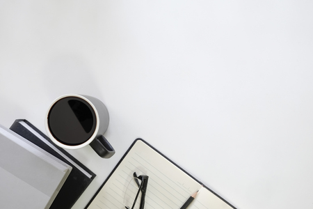 Copy space table with book, coffee cup, pencil,notebook and glasses on desk.
