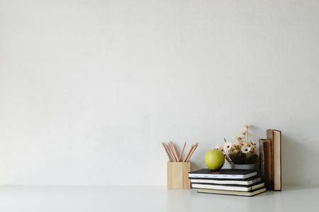 Mockup table with plant decorate, cup of coffee, book, green apple and jar of pencil on white table and white background.