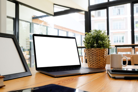 Mockup laptop computer on wooden table in office workspace. Stock Photo