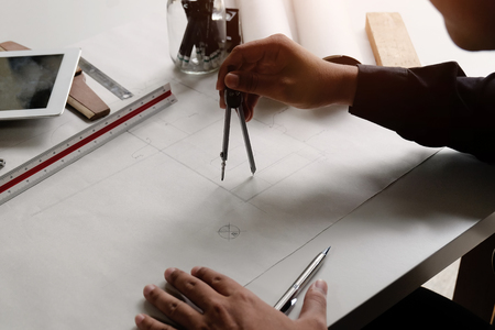 Architecture drawing on blueprint paper with dividers on hands.