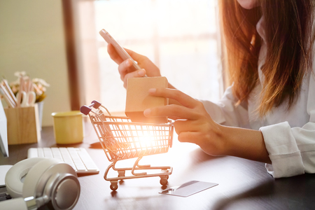 Boxes in a trolley with Woman hands, Shopping online concept. Stock Photo