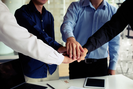 Business people putting their hands on top of office desk cooperation concept.
