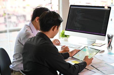 Ein Programmierer mit zwei Männern, der mit Laptop arbeitet und am Computer codiert.