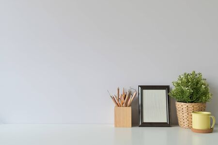 pencil, coffee, photo frame and plant on copy space, office desk.