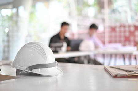 Architectural Office desk construction project with drawing equipment and engineer helmet.