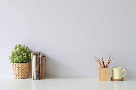 Workspace with books, coffee, pencil and plant decoration on office white desk.