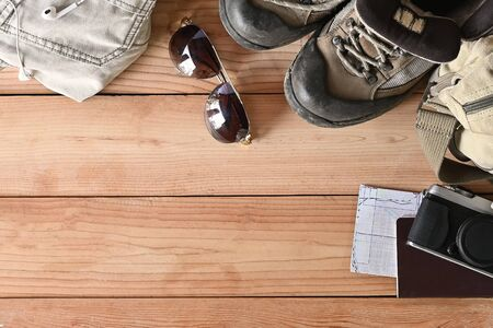 Travel accessories set on wooden desk hiking boots, jacket, backpack, map, camera and sunglasses with copy space.