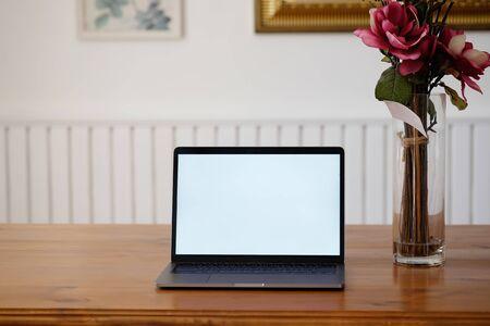 Mockup laptop computer and rose flower on wooden office desk. Stok Fotoğraf