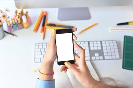 Mockup smartphone on woman hands using on office workspace.