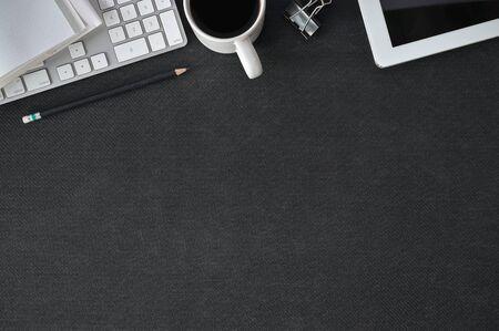 Scrivania da ufficio in pelle nera con computer, forniture per ufficio e tazza di caffè. Vista dall'alto con spazio di copia. Archivio Fotografico