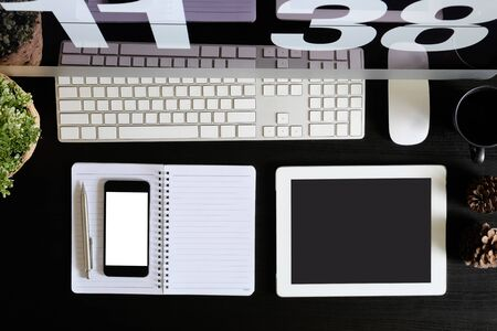 Office desk with tablet and smartphone mockup on black wooden table, A top view shot.