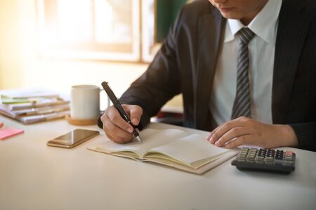 Businessman doing finances and calculate on office desk about cost at home office.