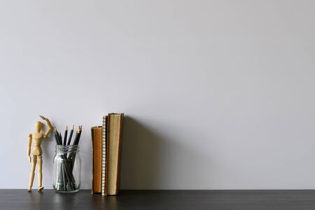 Copy space office desk with pencil, books and wood dummy model on table.