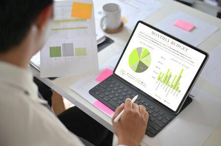 Businessman analyzing financial statistics displayed on the tablet screen. Stok Fotoğraf