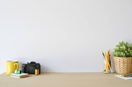 Creative workspace camera and office supplies on wood desk with copy space. Stock Photo