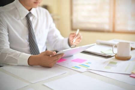 Closeup businessman analysis data in digital tablet on office desk.