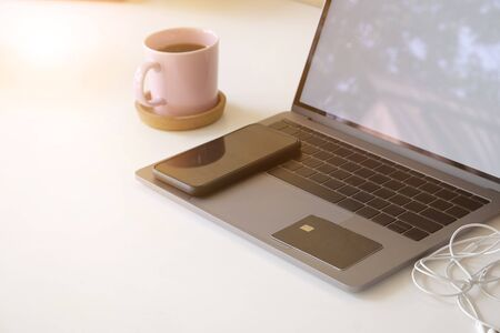 Credit card and smartphone on laptop computer and coffee cup with office table.