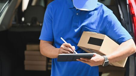 Delivery man checking list on tablet computer.