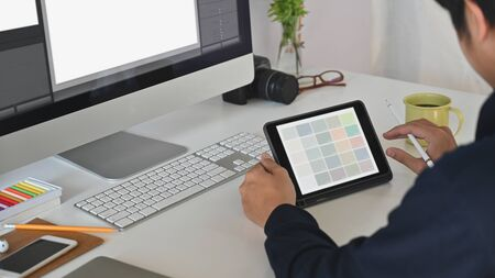 Young creative man giving concentrate on his tablet.