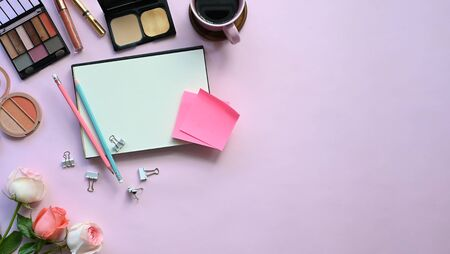 Top view of woman accessories putting on the pink working desk, including keyboard, coffee cup, bouquet, notebook, pen, women cosmetics and paper clip. Feminine working desk concept.