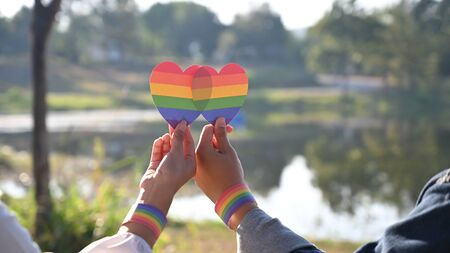 Closeup of LGBT couple while they are holding a rainbow hearts on hand. LGBT happiness concept.